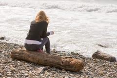 Ragazza che si siede sul collegamento la costa e gli sguardi in mare fotografia stock libera da diritti