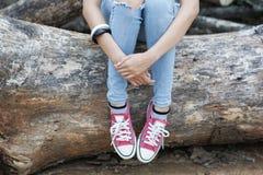 Ragazza che si siede sul legname Immagine Stock