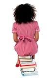 Ragazza che si siede sul mucchio dei libri che affrontano la parete Fotografia Stock