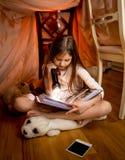 Ragazza che si siede sul pavimento al libro di lettura e della camera da letto con flashligh Fotografia Stock Libera da Diritti