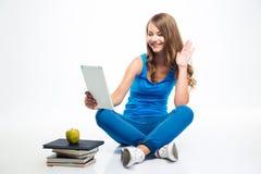 Ragazza che si siede sul pavimento con il computer della compressa Fotografie Stock Libere da Diritti