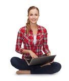 Ragazza che si siede sul pavimento con il computer portatile Fotografia Stock