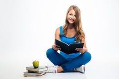 Ragazza che si siede sul pavimento con il libro Immagini Stock Libere da Diritti