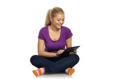 Ragazza che si siede sul pavimento con la compressa Fotografia Stock Libera da Diritti