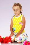 Ragazza che si siede sul pavimento vicino ai fiori rossi Fotografia Stock