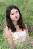 Ragazza che si siede sul prato con i fiori Fotografie Stock