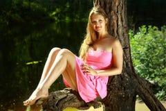 Ragazza che si siede sul ramo del pino, vicino al lago della foresta. Fotografie Stock