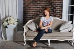 Ragazza che si siede sul sofà Fotografia Stock Libera da Diritti