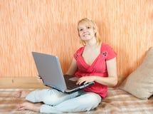 Ragazza che si siede sul sofà con il computer portatile Immagine Stock Libera da Diritti