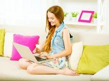 Ragazza che si siede sul sofà e che scrive sul computer portatile Fotografie Stock Libere da Diritti