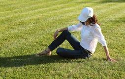 Ragazza che si siede sull'erba Immagini Stock
