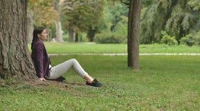 Ragazza che si siede sull'erba Fotografia Stock Libera da Diritti