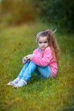 Ragazza che si siede sull'erba Fotografie Stock