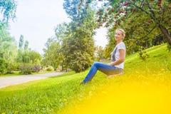 Ragazza che si siede sull'erba Immagine Stock