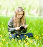 Ragazza che si siede sull'erba con i denti di leone e che legge un libro Fotografie Stock