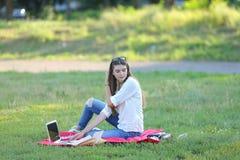 Ragazza che si siede sull'erba nel parco e sugli impianti ad un computer portatile Fotografie Stock Libere da Diritti