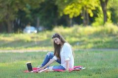Ragazza che si siede sull'erba nel parco e sugli impianti ad un computer portatile Fotografia Stock