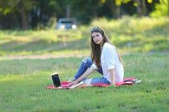 Ragazza che si siede sull'erba nel parco e sugli impianti ad un computer portatile Fotografia Stock Libera da Diritti