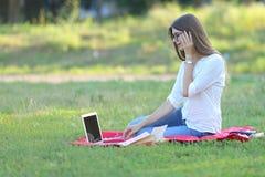 Ragazza che si siede sull'erba nel parco e sugli impianti ad un computer portatile Immagine Stock