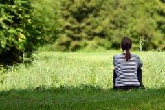 Ragazza che si siede sull'erba verde Immagine Stock Libera da Diritti