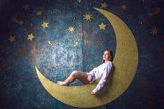 Ragazza che si siede sulla luna Immagine Stock