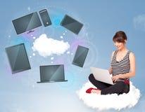 Ragazza che si siede sulla nuvola che gode del servizio in rete della nuvola Fotografia Stock