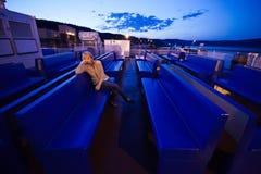 Ragazza stanca che si siede sulla piattaforma Fotografie Stock Libere da Diritti