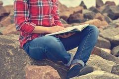 Ragazza che si siede sulla roccia e che legge un libro Fotografie Stock Libere da Diritti