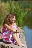 Ragazza che si siede sulla roccia mentre distogliendo lo sguardo dal lago fotografia stock