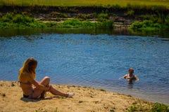 Ragazza che si siede sulla sabbia alla spiaggia Con suo di nuovo alla macchina fotografica Fondo immagine stock