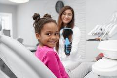 Ragazza che si siede sulla sedia del dentista che esamina macchina fotografica e sorridere immagini stock libere da diritti