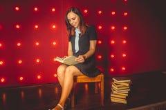 ragazza che si siede sulla sedia e che legge un libro fotografia stock libera da diritti