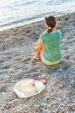 Ragazza che si siede sulla spiaggia Fotografia Stock Libera da Diritti