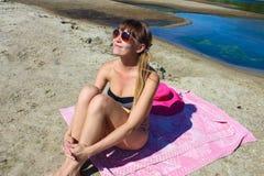 Ragazza che si siede sulla spiaggia Immagine Stock