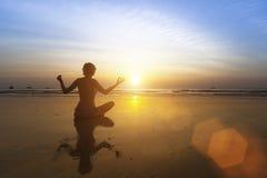 Ragazza che si siede sulla spiaggia durante il tramonto e che medita nella posa di yoga Fotografia Stock