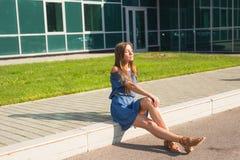 Ragazza che si siede sulla via nel giorno di estate Fotografia Stock Libera da Diritti