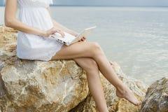 Ragazza che si siede sulle rocce dal mare, lavorante con un computer portatile Fotografie Stock Libere da Diritti