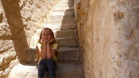 Ragazza che si siede sulle scale ai punti ed al pensiero di pietra beige video d archivio