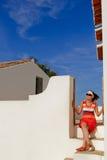 Ragazza che si siede sulle scale fronte fuori della casa bianca Fotografia Stock