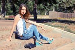 Ragazza che si siede sulle scale nel giorno di estate caldo Fotografie Stock