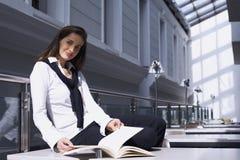 Ragazza che si siede sullo scrittorio in libreria Fotografia Stock