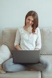 Ragazza che si siede sullo strato con un computer portatile Fotografie Stock