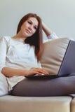 Ragazza che si siede sullo strato con un computer portatile Fotografia Stock Libera da Diritti