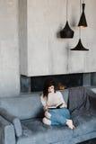 Ragazza che si siede sullo strato Stanza nello stile del sottotetto Stanza con un camino lettura della ragazza del libro Una raga Fotografie Stock