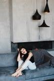 Ragazza che si siede sullo strato Stanza nello stile del sottotetto Stanza con un camino Ragazza sorridente felice Ragazza Immagine Stock