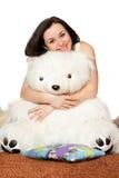 ragazza che si siede in un abbraccio con un orso di orsacchiotto Immagini Stock