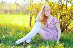 Ragazza che si siede in un giardino di fioritura della molla Fotografia Stock