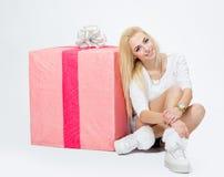 Ragazza che si siede vicino ad un grande regalo, sul fondo bianco fotografia stock libera da diritti