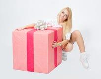 Ragazza che si siede vicino ad un grande regalo, sul fondo bianco immagine stock libera da diritti