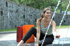 Ragazza che si siede vicino ad una fontana immagine stock